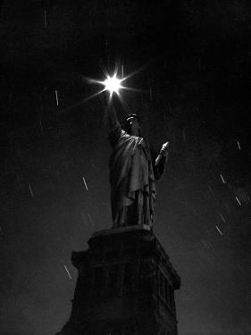 Long Exposure of the Statue of Liberty at Night by Andreas Feininger