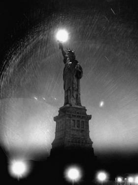 Misty Night Surrounding the Statue of Liberty with Fuzzy Balls of Light from Torch and Lampposts by Andreas Feininger