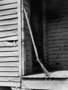 Old Rifle Leaning Up a Wall on the Porch of an Old House by Andreas Feininger