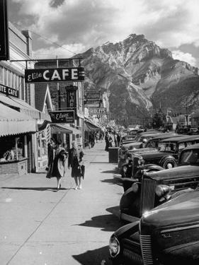 Pedestrians Walking Along Main Street in Resort Town with Cascade Mountain in the Background by Andreas Feininger