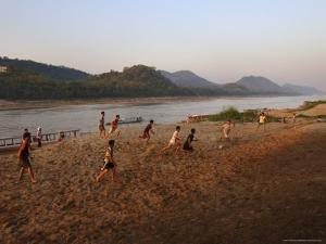 Playing Football on the Banks of the Mekong River, Luang Prabang, Laos, Indochina by Andrew Mcconnell