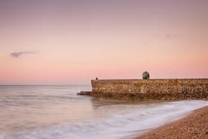 Fisherman and the Green Doughnut sculpture at dawn on Brighton Seafront, Brighton, East Sussex, Eng by Andrew Sproule