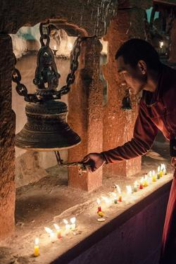 A Buddhist Monk Rings a Prayer Bell During the Full Moon Celebrations by Andrew Taylor