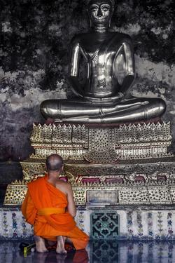 A Monk Prays in Front of a Golden Buddha, Wat Suthat, Bangkok, Thailand, Southeast Asia, Asia by Andrew Taylor