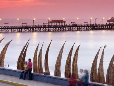 Waterfront Scene at Huanchaco in Peru, Locals Relax Next to Totora Boats Stacked Along the Beach