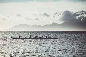 Men Paddle an Outrigger Canoe Off Tahiti Island, with Moorea Island in the Background by Andy Bardon