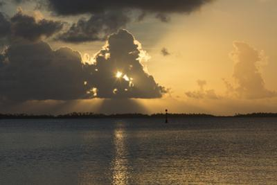 Sun Rays Filter Through Dramatic Clouds over the Ahe Atoll at Sunset by Andy Bardon