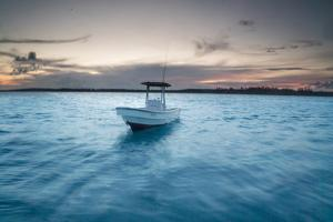 A Skiff Anchored Off the Coast of Cat Island in the Bahamas at Sunset by Andy Mann