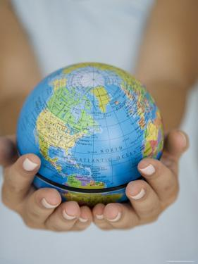 Woman's Hands Holding World Globe by Angelo Cavalli