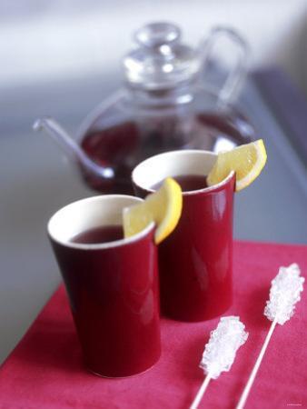 Two Beakers of Fruit Tea with Lemon Wedges, Sugar Sticks