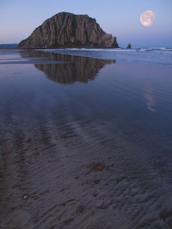 USA, California. Morro Rock reflecting in wet sand at moonrise. by Anna Miller