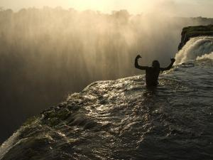 Bathing in a Swimming Hole at the Top of Victoria Falls by Annie Griffiths Belt