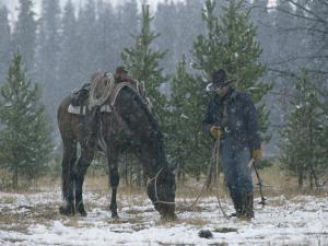 Snow Falls on an Outfitter Grazing His Tacked Horse by Annie Griffiths Belt