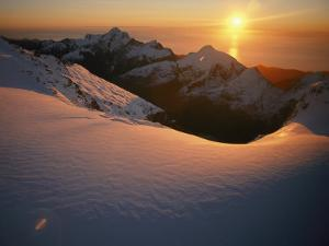 Sunset Glow over a Snowy Mountain Face by Annie Griffiths Belt