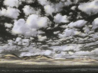Puffy Clouds Fill a Sky Above Gentle Rolling Hills in the Distance by Annie Griffiths