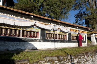 Buddhist Monk in Red Robes Turning Prayer Wheels in Contemplative Morning Prayer