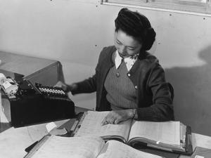 Mrs Teruko Kiyomura, bookkeeper, seated at desk, operating an adding machine while reading a ledger by Ansel Adams