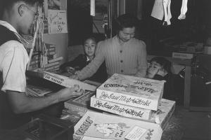 Mrs. Yaeko Nakamura shows her daughters jigsaw puzzles in a store at Manzanar, 1943 by Ansel Adams
