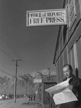 Roy Takeno, editor of Manzanar Free Press, reading the paper at the Manzanar War Relocation Center by Ansel Adams
