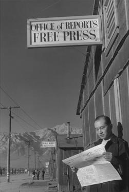 Roy Takeno Reading Paper in Front of Office by Ansel Adams