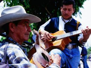 Men Strumming Guitars in Parque Libertad, San Salvador, El Salvador by Anthony Plummer
