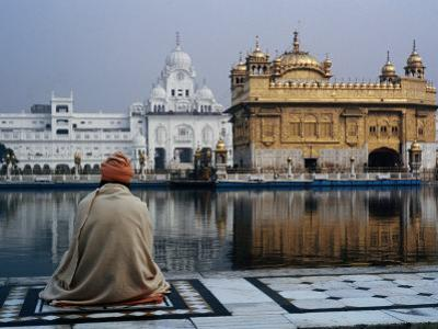 Sikh Man Meditating in Front of the Golden Temple, Amritsar, India by Anthony Plummer