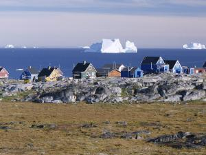 Painted Village Houses in Front of Icebergs in Disko Bay, West Coast, Greenland by Anthony Waltham