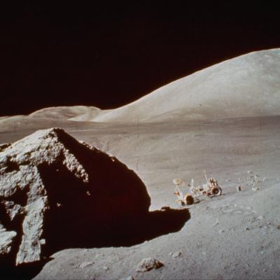 Apollo 17's Rover, a Lunar Vehicle, on the Surface of the Moon Next to Giant Rock