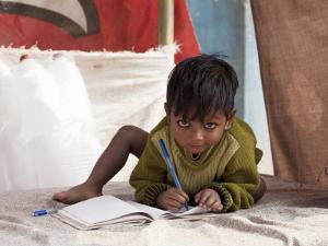 Boy Writing in Notebook by April Maciborka