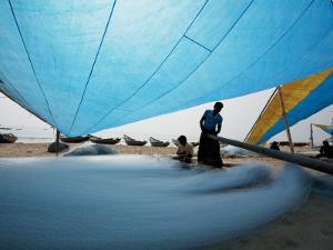 Fishermen Repairing their Nets under Shade of Sail by April Maciborka