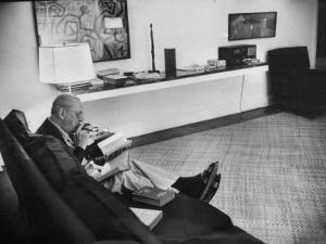 Architect Mies Van Der Rohe Relaxing on Couch While Smoking Cigar and Reading at Home