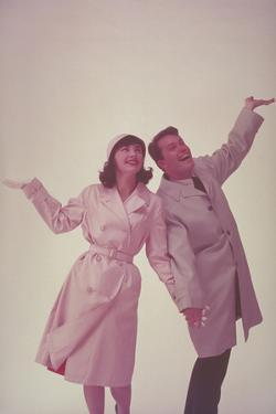 COUPLE IN RAINCOAT WITH HANDS Up, 1962 by Archive Holdings Inc.