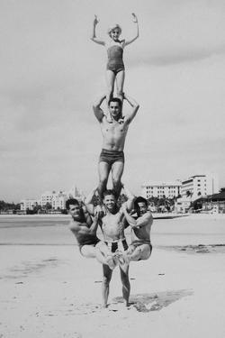 MEN AND GIRL PERFORM ACROBATICS ON BEACH by Archive Holdings Inc.