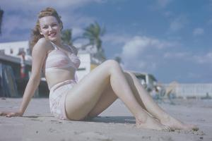 WOMAN SEATED ON BEACH IN PINK Bikini, 1940 by Archive Holdings Inc.