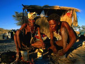 Kalahri Bushmen Cooking on Fire Outside Their Grass Homestead, South Africa by Ariadne Van Zandbergen