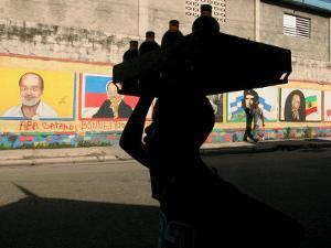 A Boy Carrying Bottles on His Head Passes by a Wall with Pictures of Haitian President Renel Preval by Ariana Cubillos