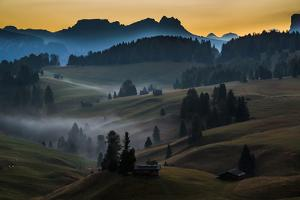 A small village on rolling hills as the sun rises over the Dolomites, Italy by Art Wolfe