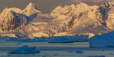 Morning light shines on the mountains and Icebergs, Antarctica by Art Wolfe