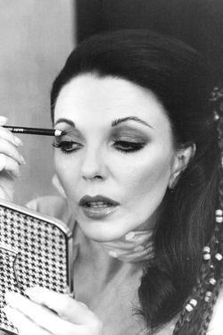 Joan Collins Applying Makeup by Associated Newspapers