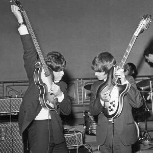 Paul Mccartney and George Harrison Tune their Guitars by Associated Newspapers