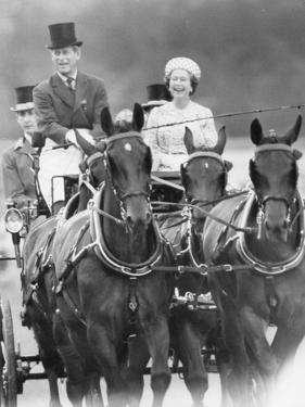 Queen Elizabeth II in a carriage being driven by Prince Philip by Associated Newspapers