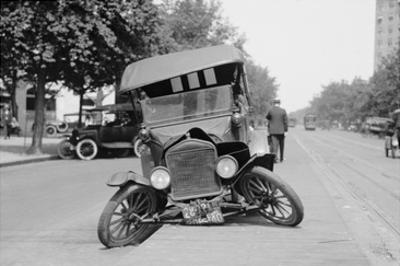 Automobile's Front Axel Breaks Splaying Tires Outward Causing Vehicle to Rest on its Front Bumper.