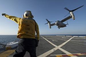 Aviation Boatswain's Mate Directs an MV-22 Osprey as it Launches from the Flight Deck