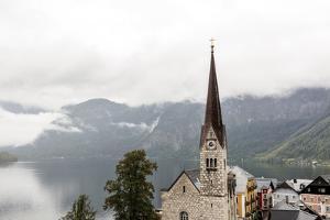 Hallstatt, Salzkammergut Region, Austria: Village By Lake On A Rainy Day With Low-Hanging Clouds by Axel Brunst