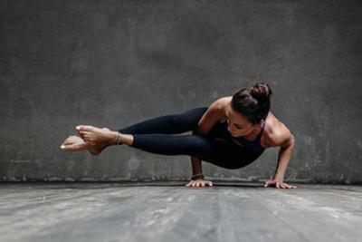 Young Beautiful Yoga Female Posing in Studio by AYakovlev