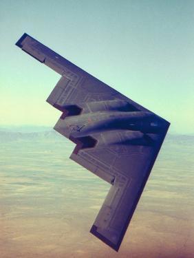 B-2 Stealth Bomber Flying over Desert-Like Landscape