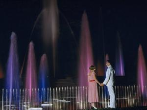 Couple Holding Hands Watches Water Fountains Illuminated at Night by B. Anthony Stewart