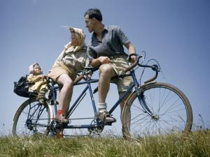 Man and Woman Straddling Tandem Bicycle Look at Child in Back Seat by B. Anthony Stewart