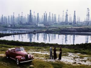 People chat by a car parked alongside a field of oil rigs, Signal Hill. by B. Anthony Stewart