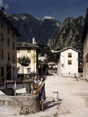 Two Girls with a Copper Pot Stand Beside Well in a Town Square by B. Anthony Stewart